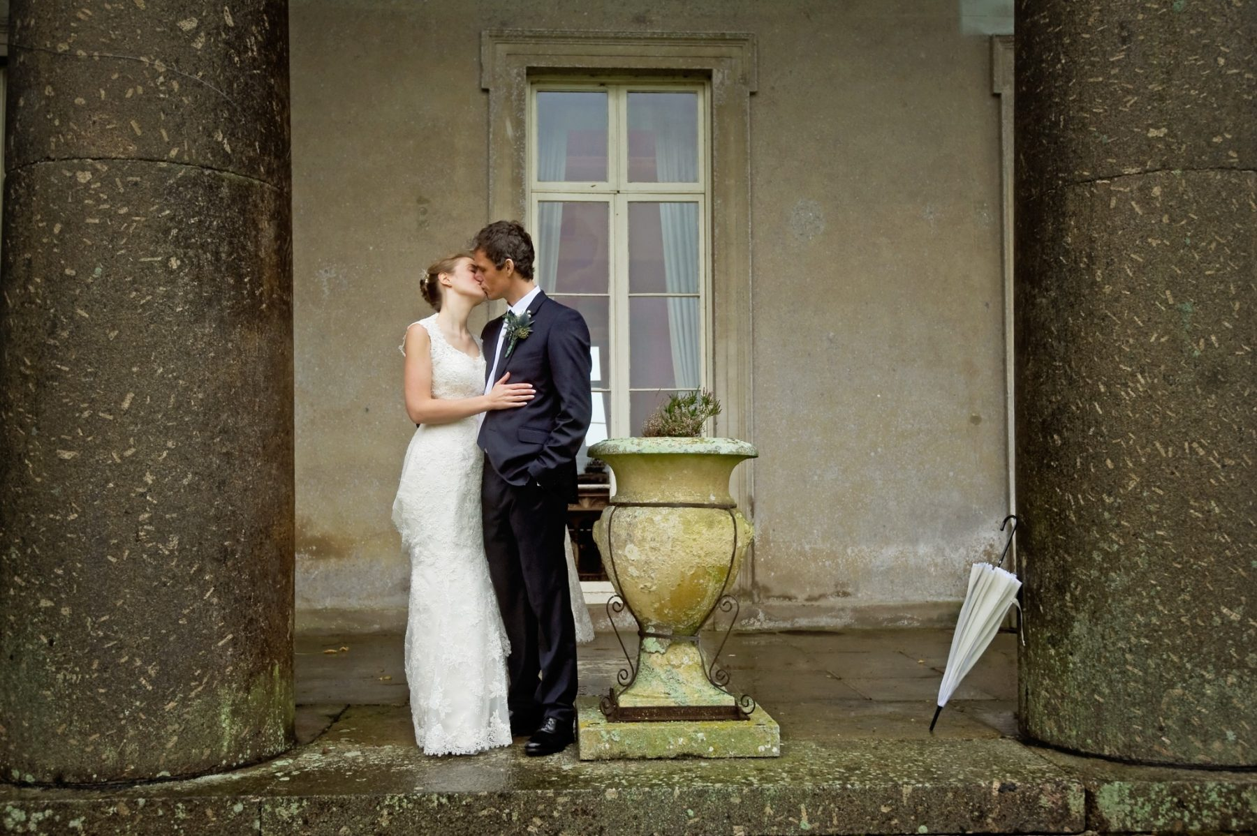 Bride and groom kiss on terrace of North Devon country house on their wedding day.