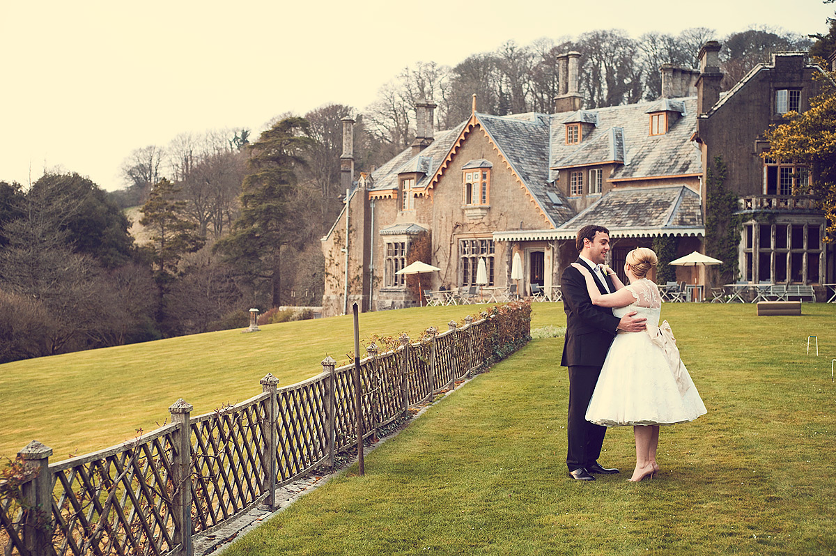 Bride and groom looking into each others eyes in front of Hotel Endsleigh