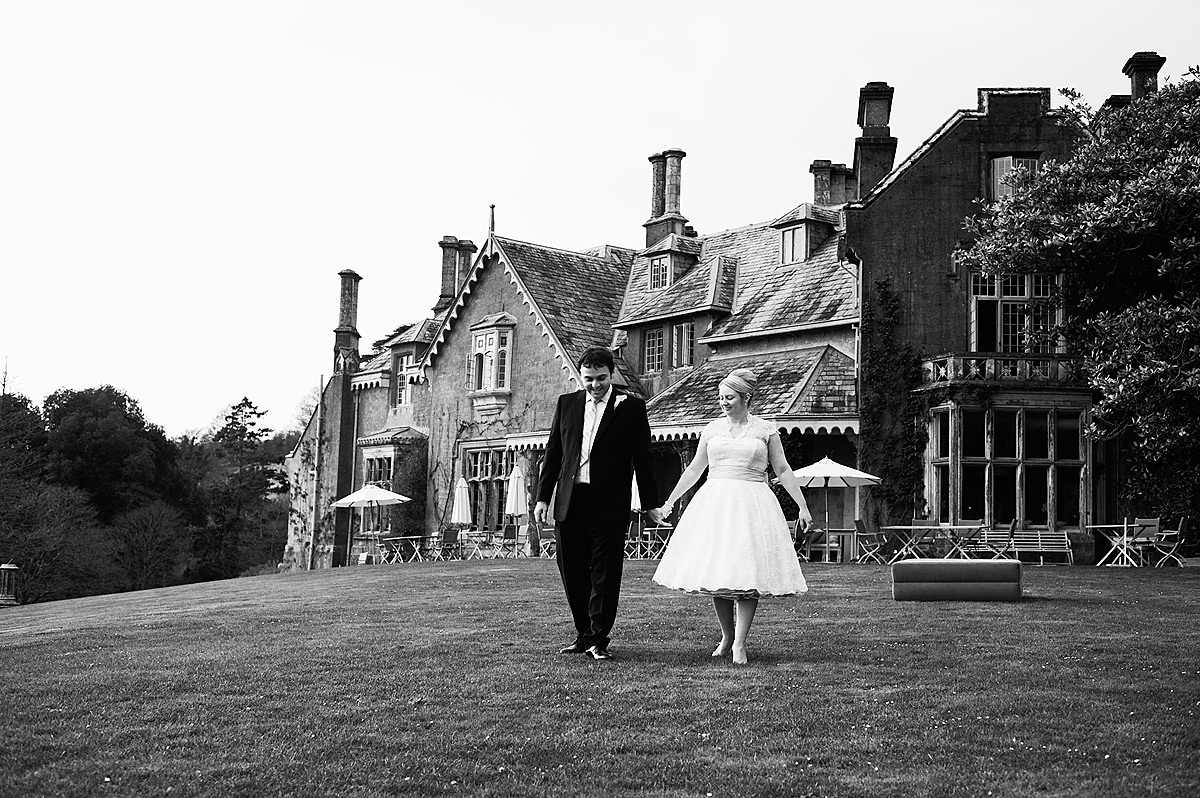 Black and white photo of bride and groom walking front of Hotel Endsleigh in Devon