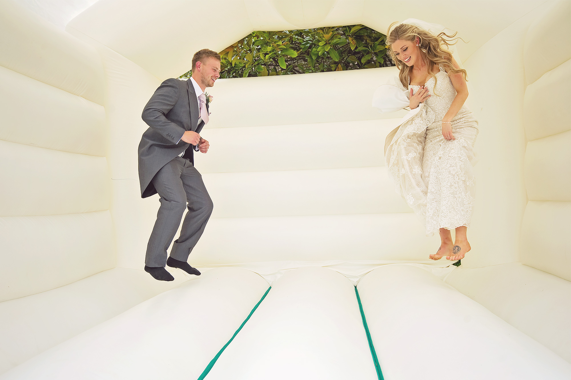 Bride and groom jumping on bouncy castle at Devon country house wedding