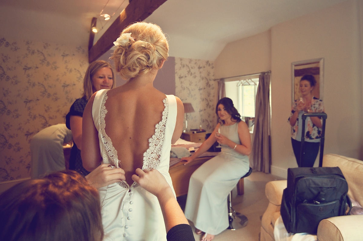 Bridesmaid looks at bride as her wedding dress is buttoned up