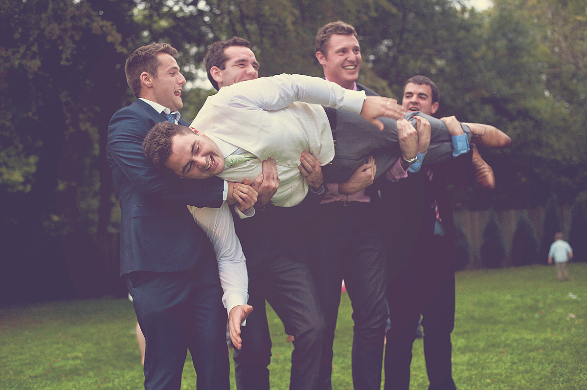 Funny photo of groom being carried by wedding guests on Dartmoor