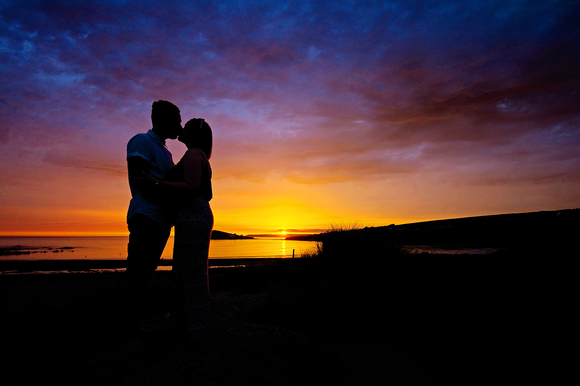 Engaged couple kissing at sunset on Bigbury beach in devon