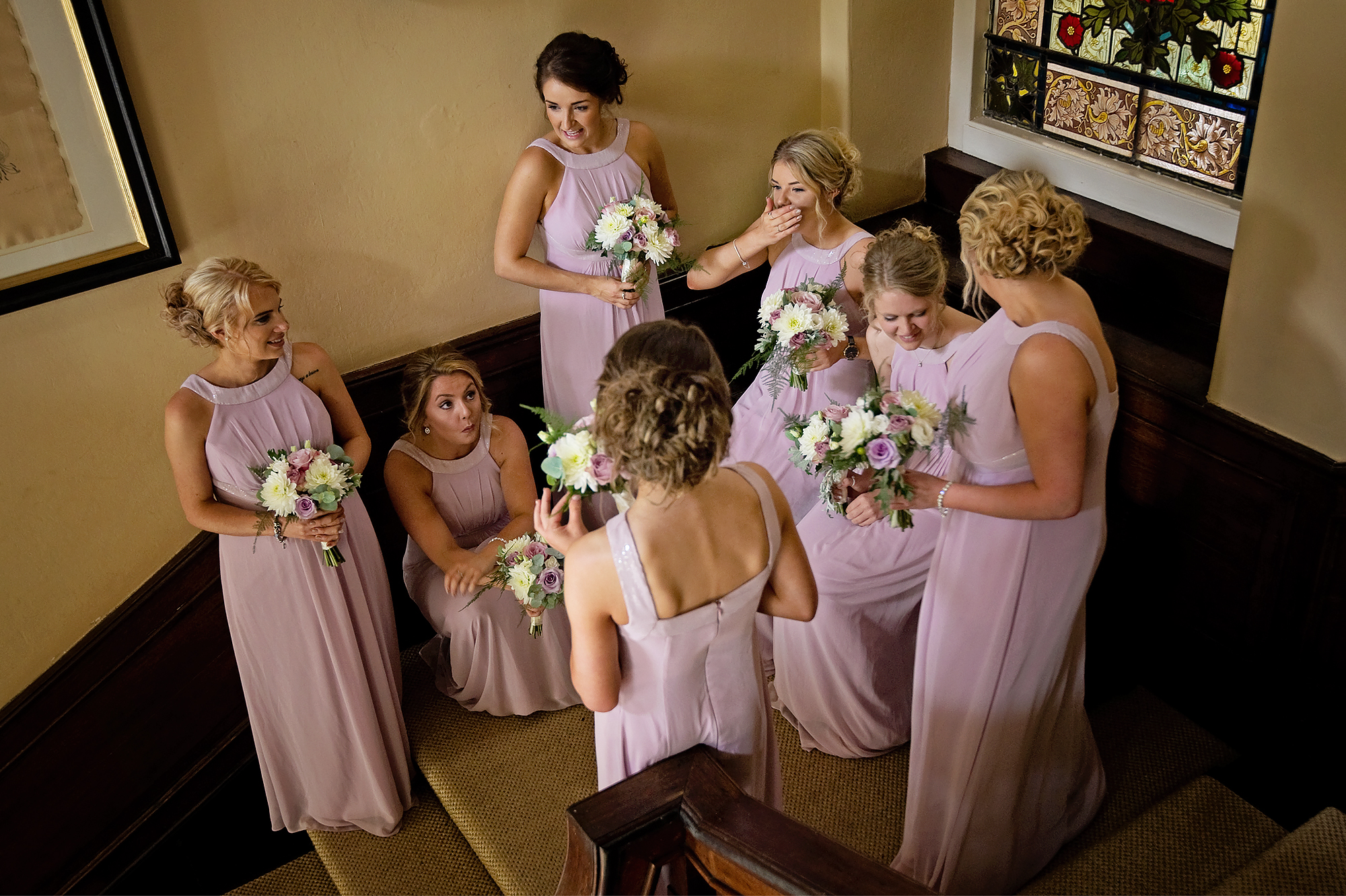 Bridesmaids in pink dresses waiting on the stairs at Langdon Court