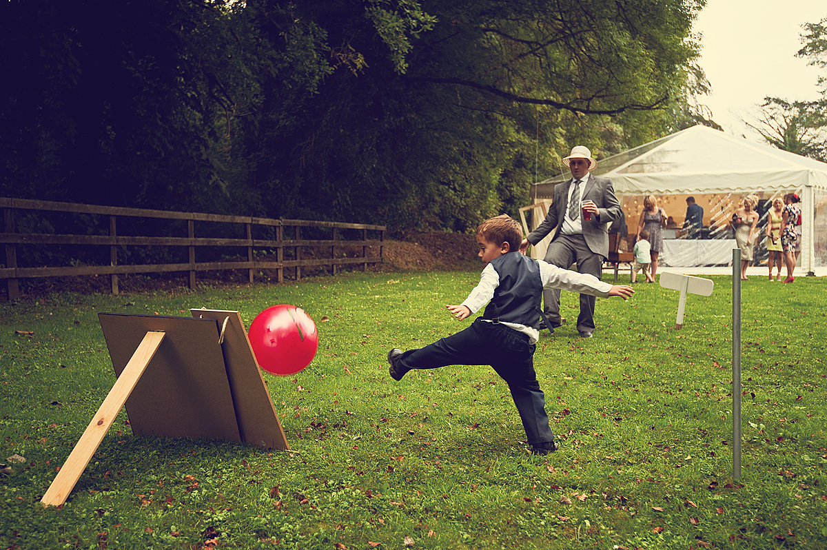 Guest and boy play football at wedding