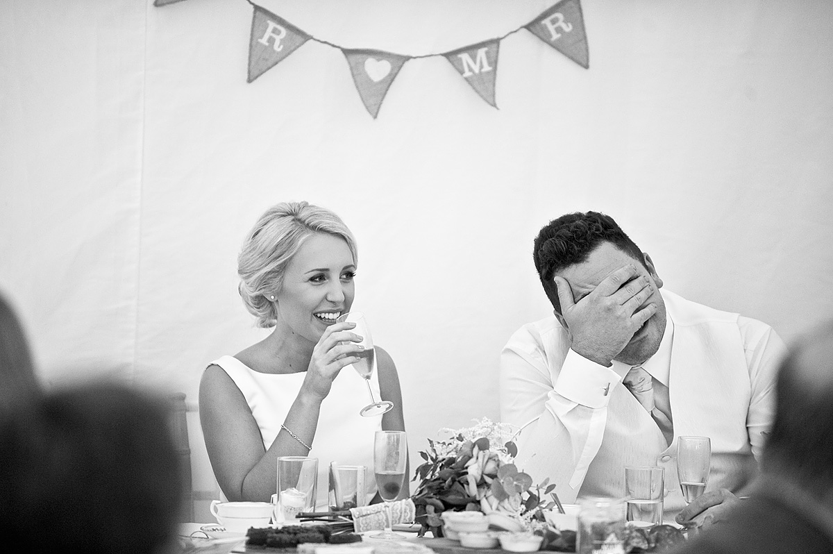 Groom covers his face with his hand during bestman wedding speech on Dartmoor