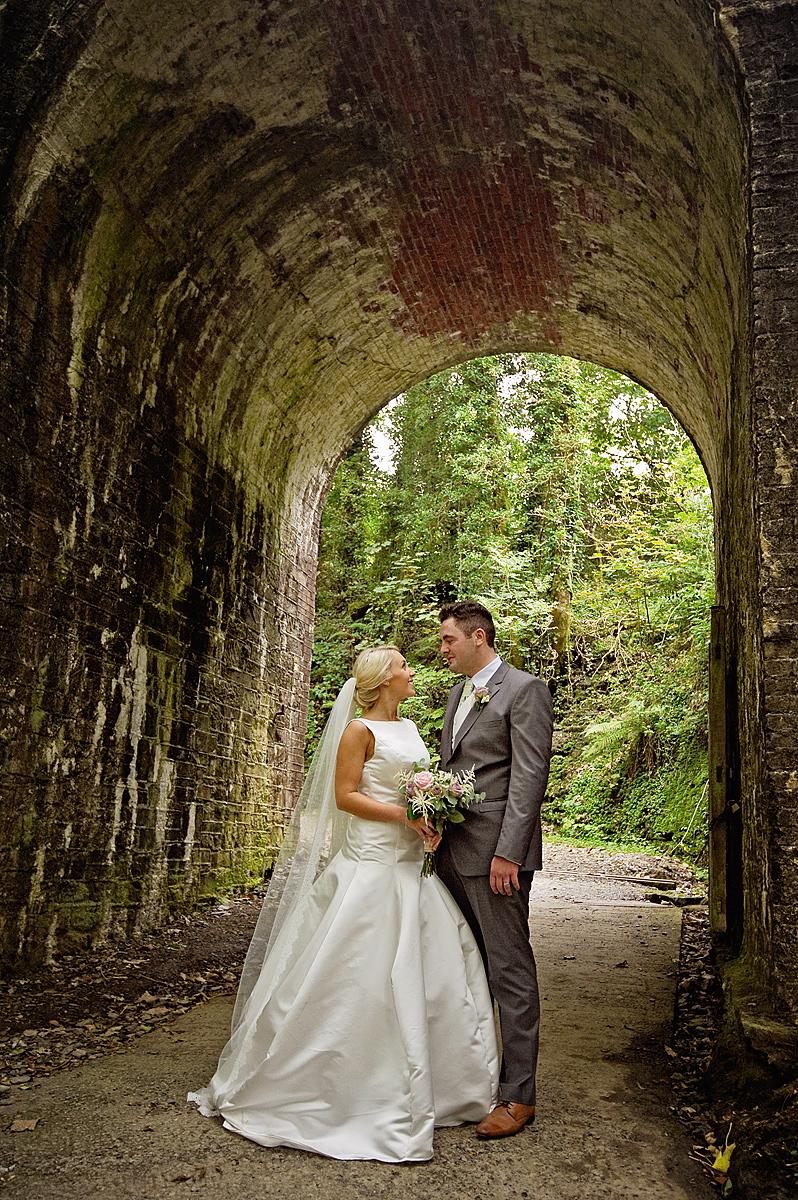 Bride and groom under railway arches at Lydford wedding