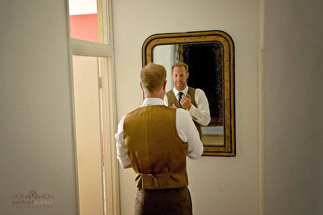 groom tieing his tie in front of mirror