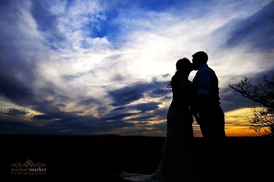 Higher Eggbeer wedding sunset silhouette kiss by bride and groom.