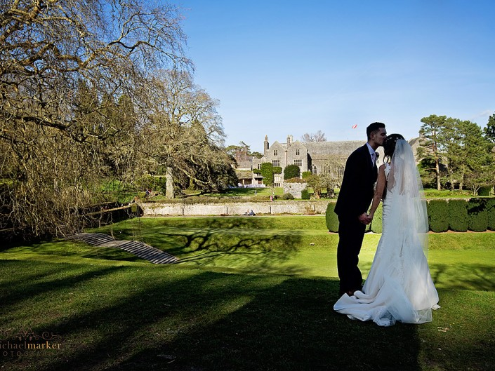 Bride and groom kiss in gardens at Dartington Hall
