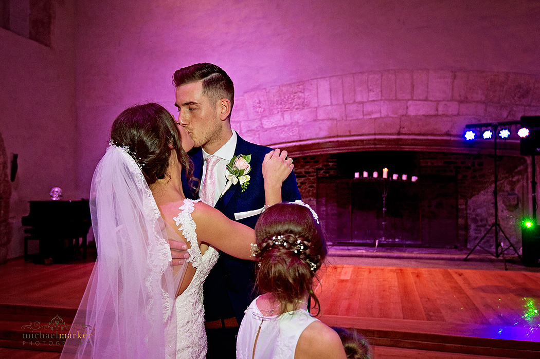 Bridesmaid looks on as bride and grooom kiss during first dance at Dartington Hall