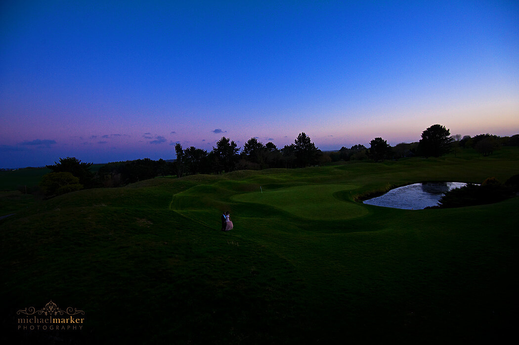 Bride and groom walk at sunset next to the heart shaped 18th hole at St Mellion golf resort in Cornwall.