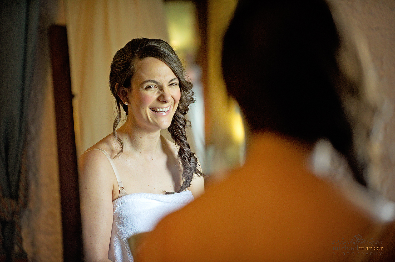 Bride laughing whilst getting ready for her wedding at Polhawn