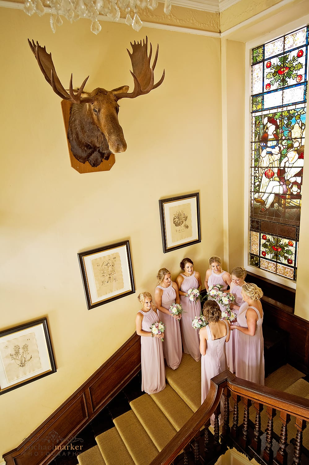 Bridesmaids waiting on the main staircase of Langdon Court under a taxidermy moose head.