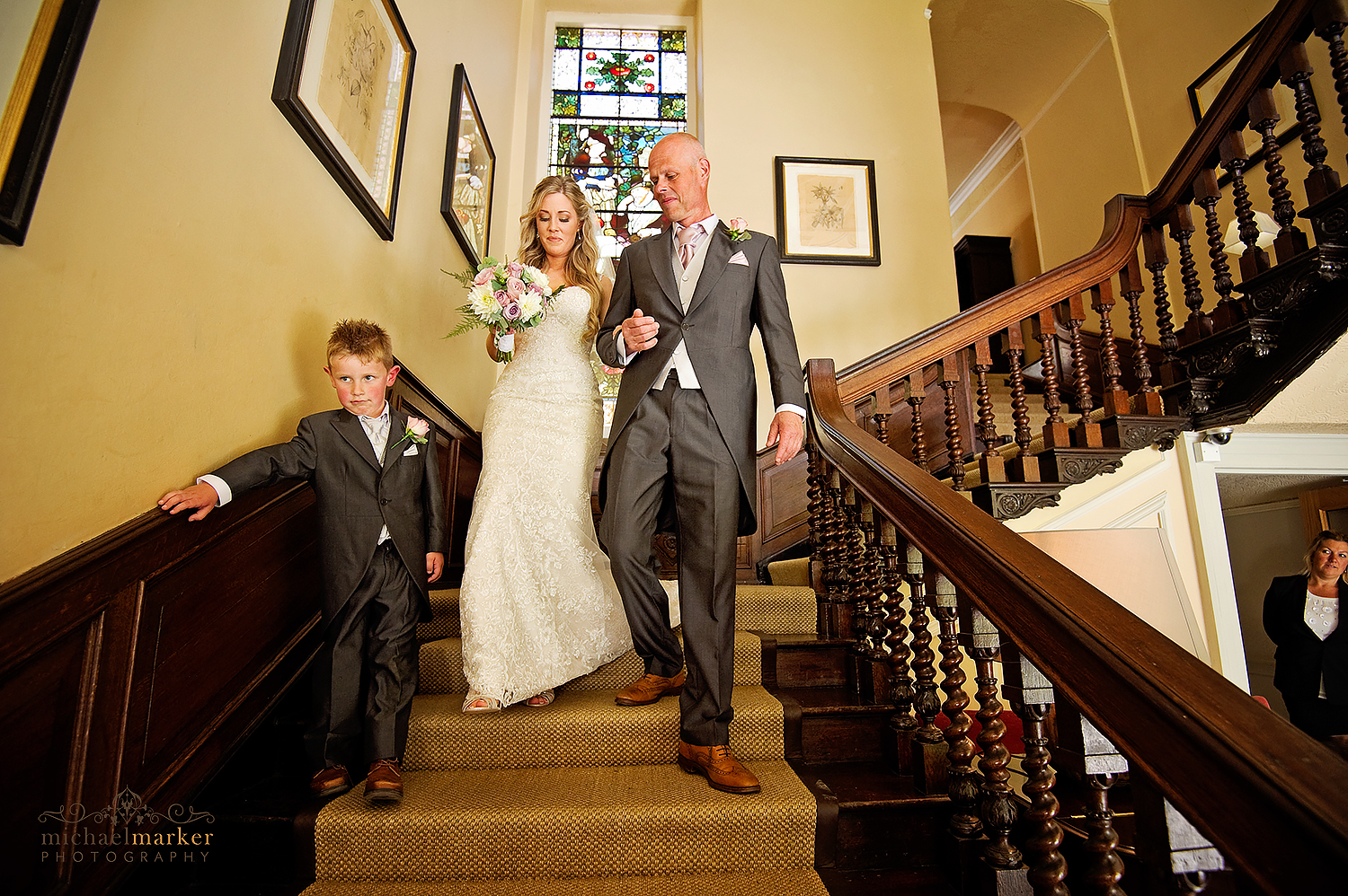 Bride and father walk down the stairs at Lamgdon Court near Wembury