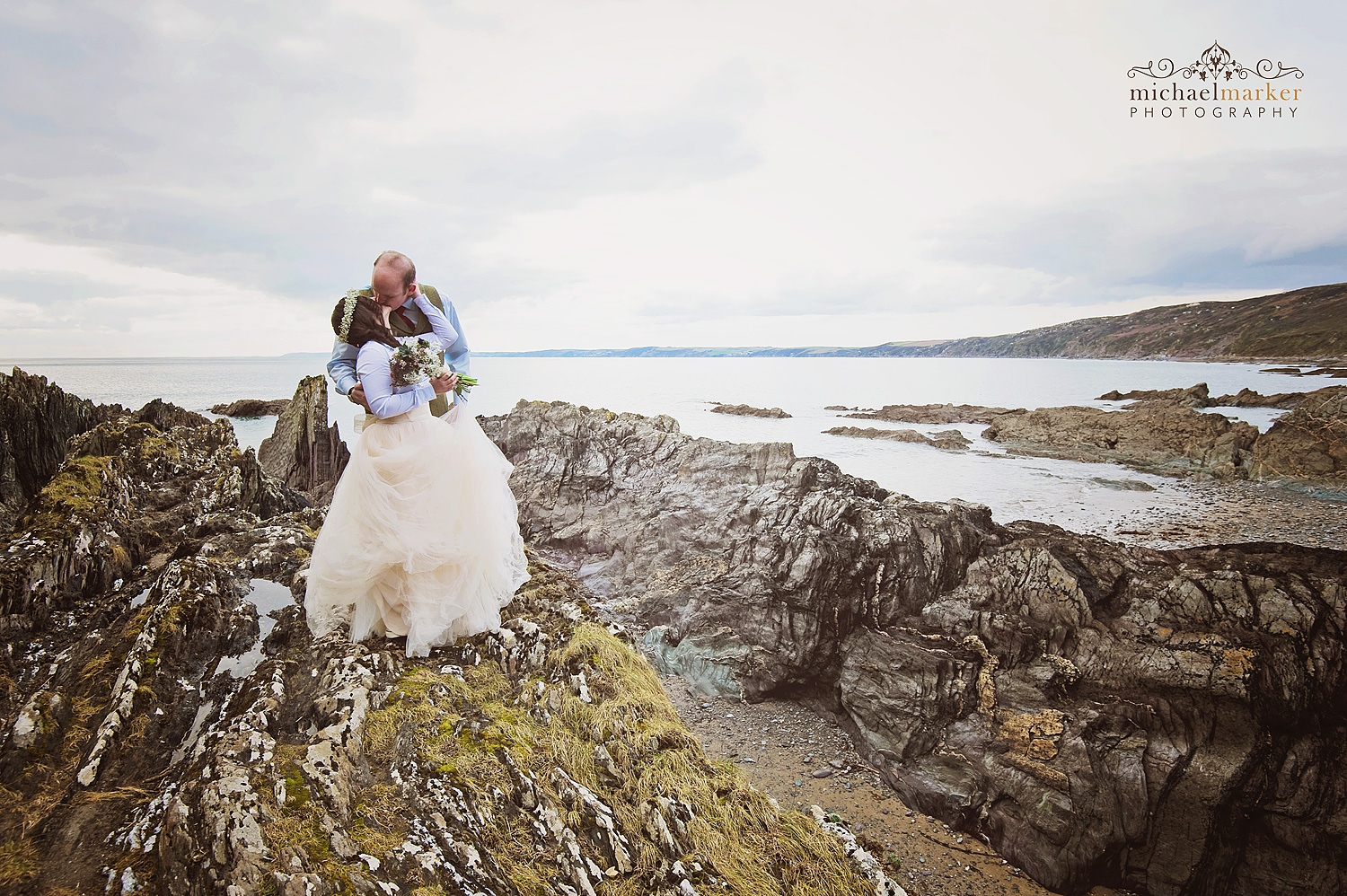 Bride and groom kiss on rocks at Cornish beach wedding