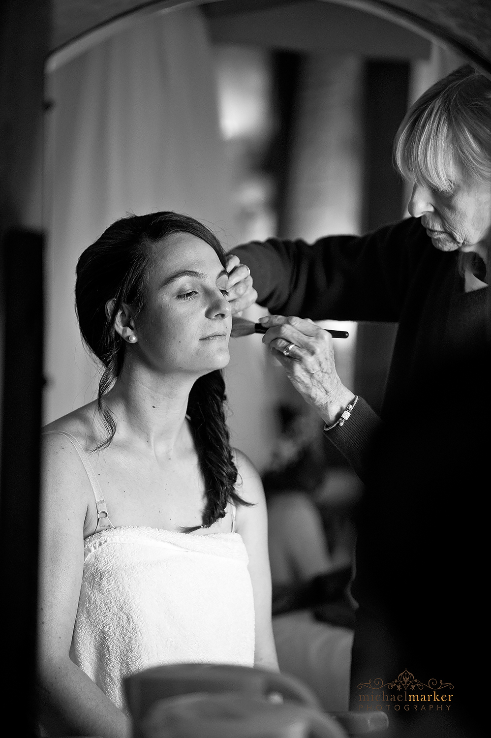 Applying blusher to bride in black and white