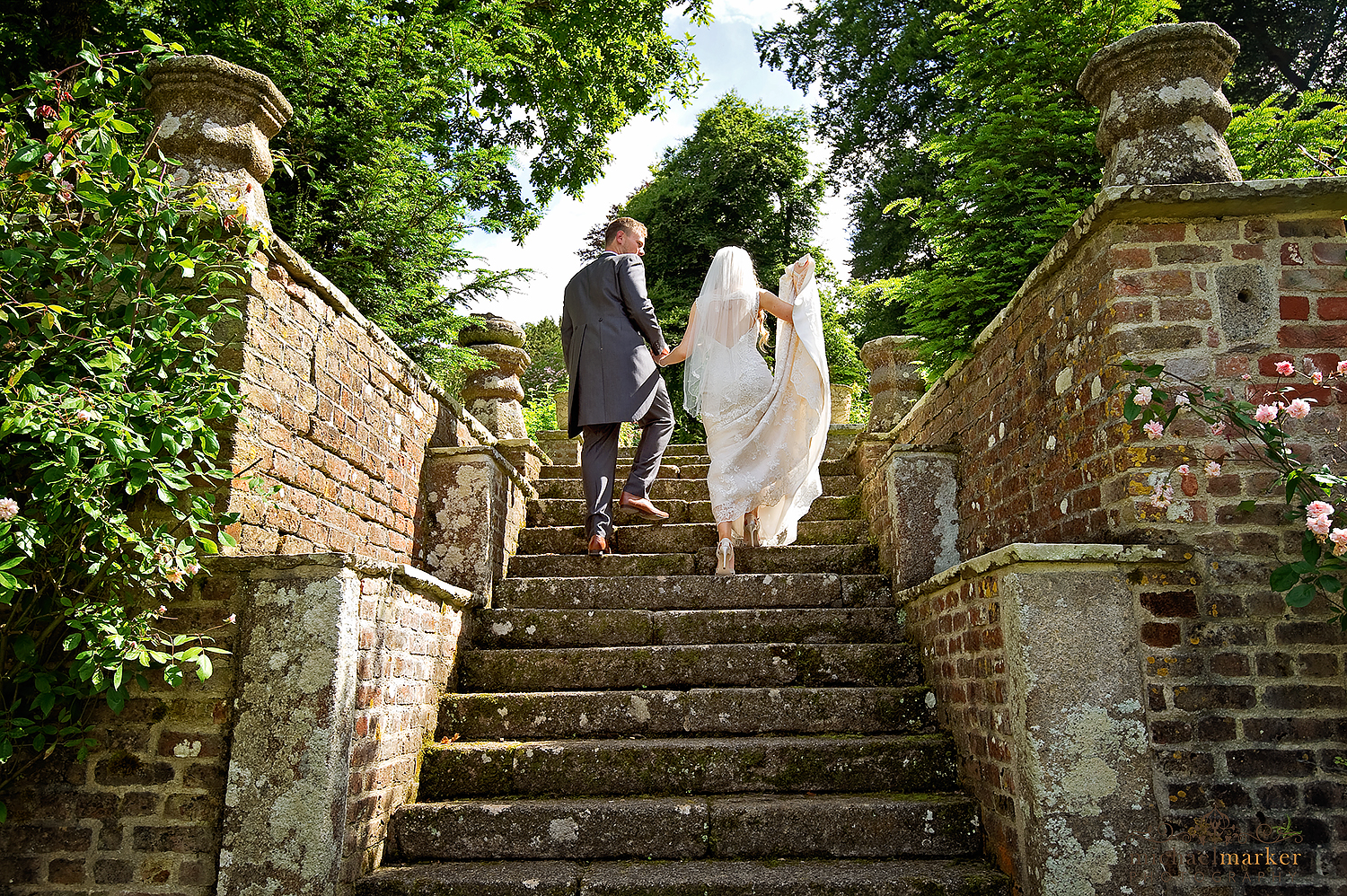 Bride and groom walk up the garden steps at Langdon Court