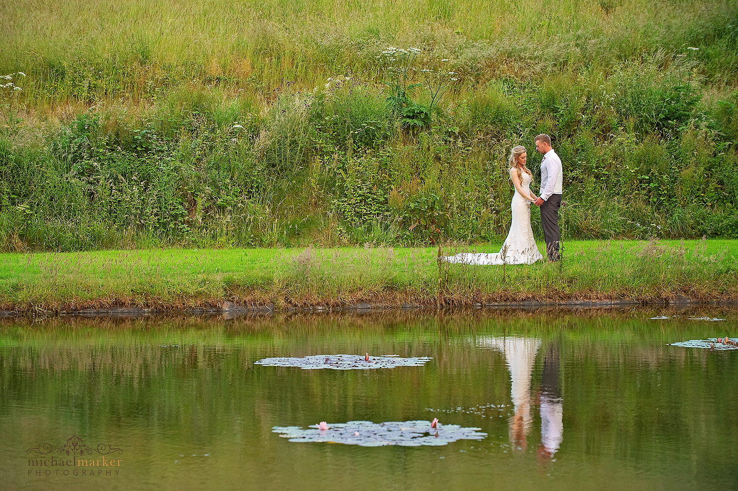 Bride and groom by the lake at Langdon Court in Devon