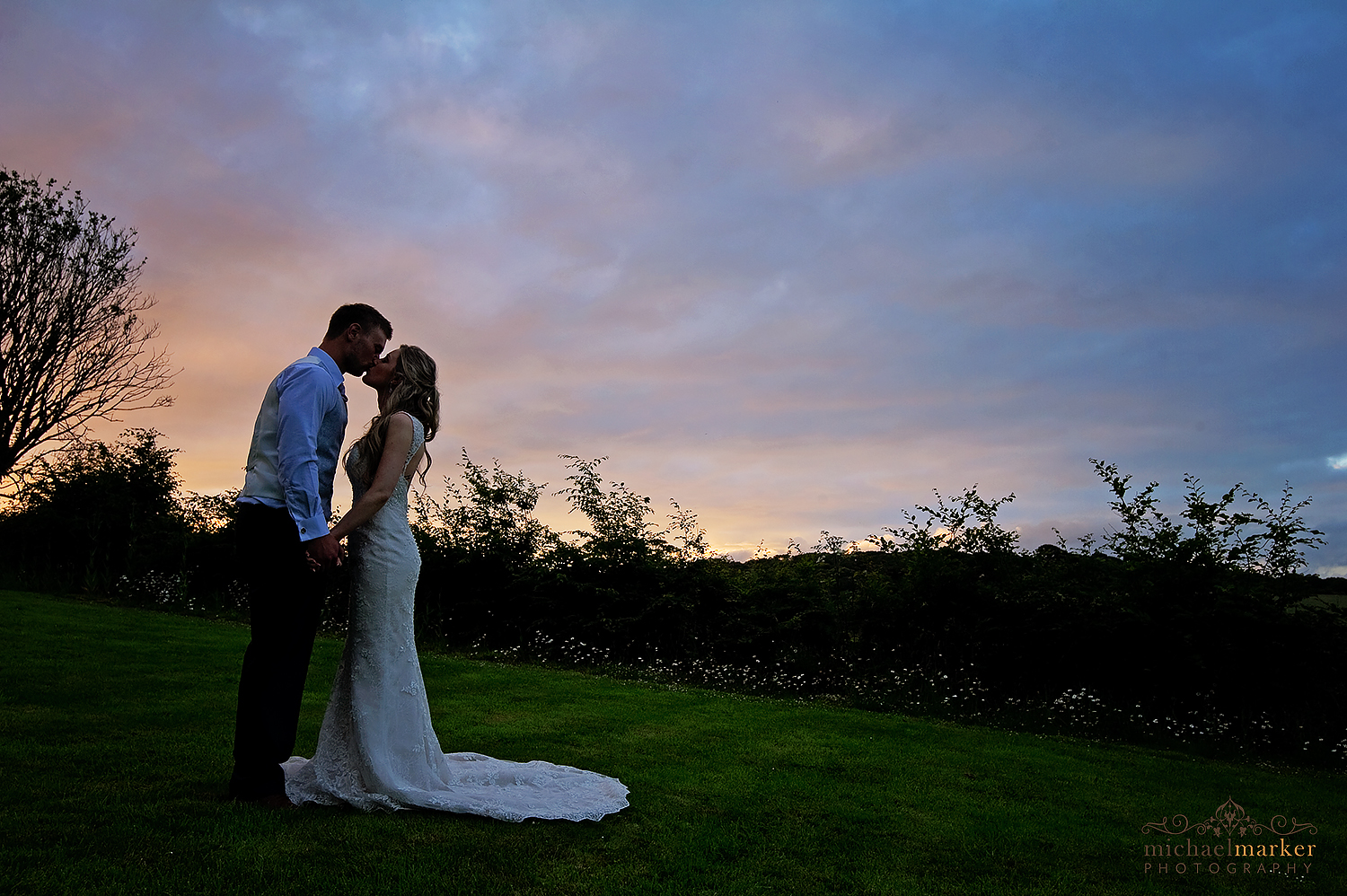 Bride and groom kiss at sunset at Langdon Court wedding