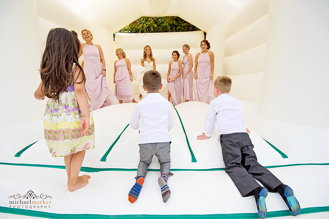 Kids watching bride and bridesmaids on bouncy castle at Devon wedding