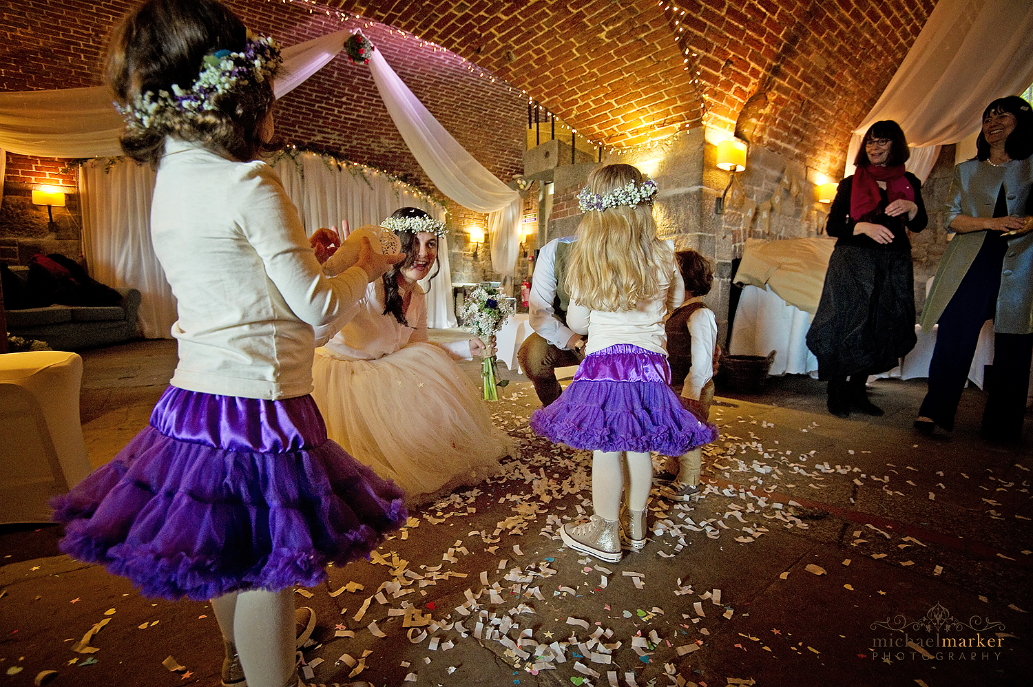 Flower girls and bride with confetti inside Polhawn fort