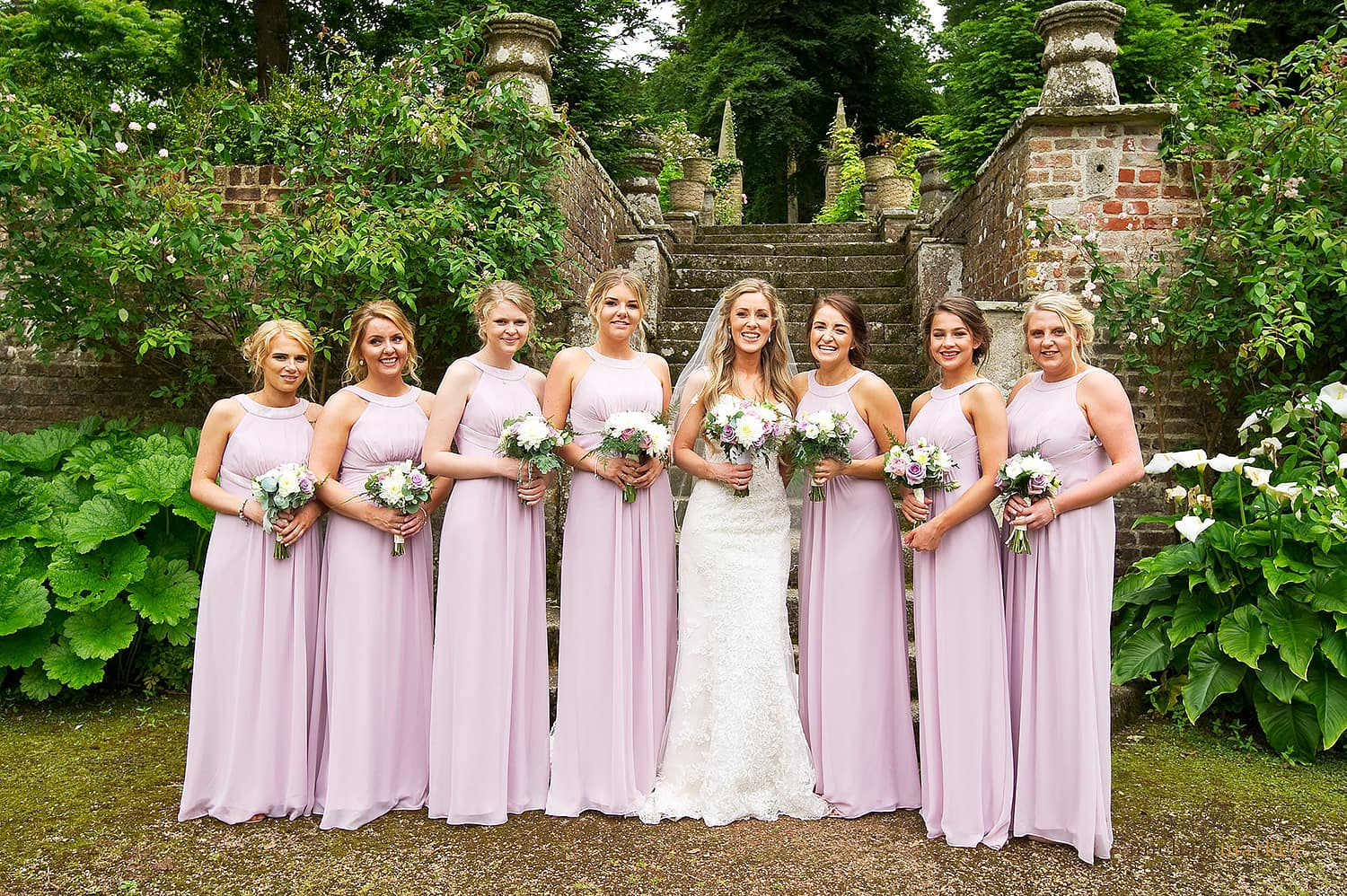 Bride and bridesmaids in pink dresses in gardens of Langdon Court in Devon.