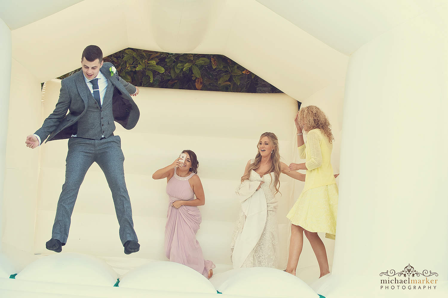 wedding guests jumping on bouncy castle