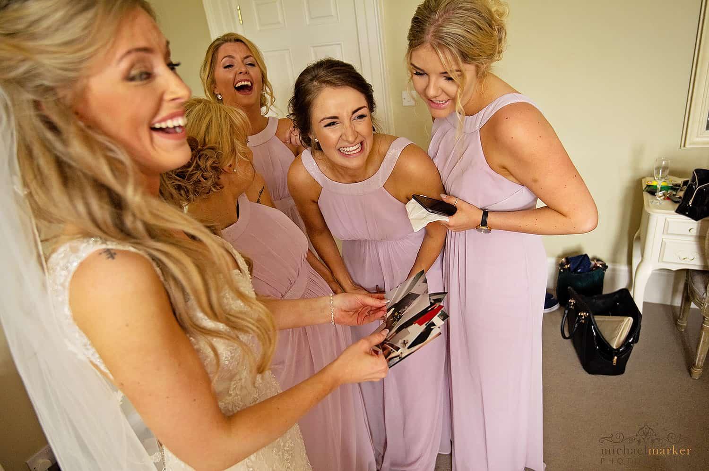 Bride and bridesmaids laughing at hen do photos