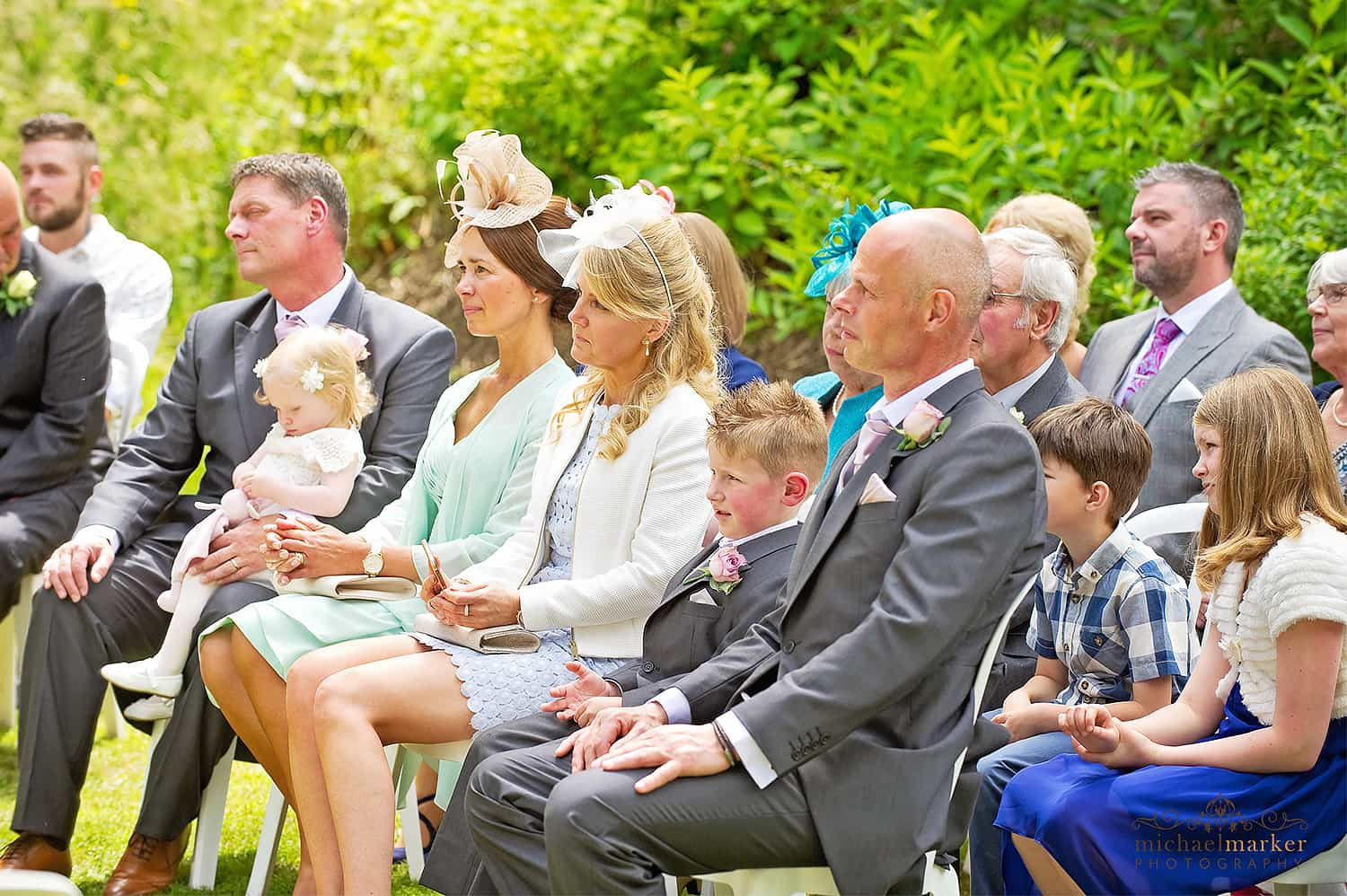 Guests watching a summer outdoor wedding ceremony at Langdon court