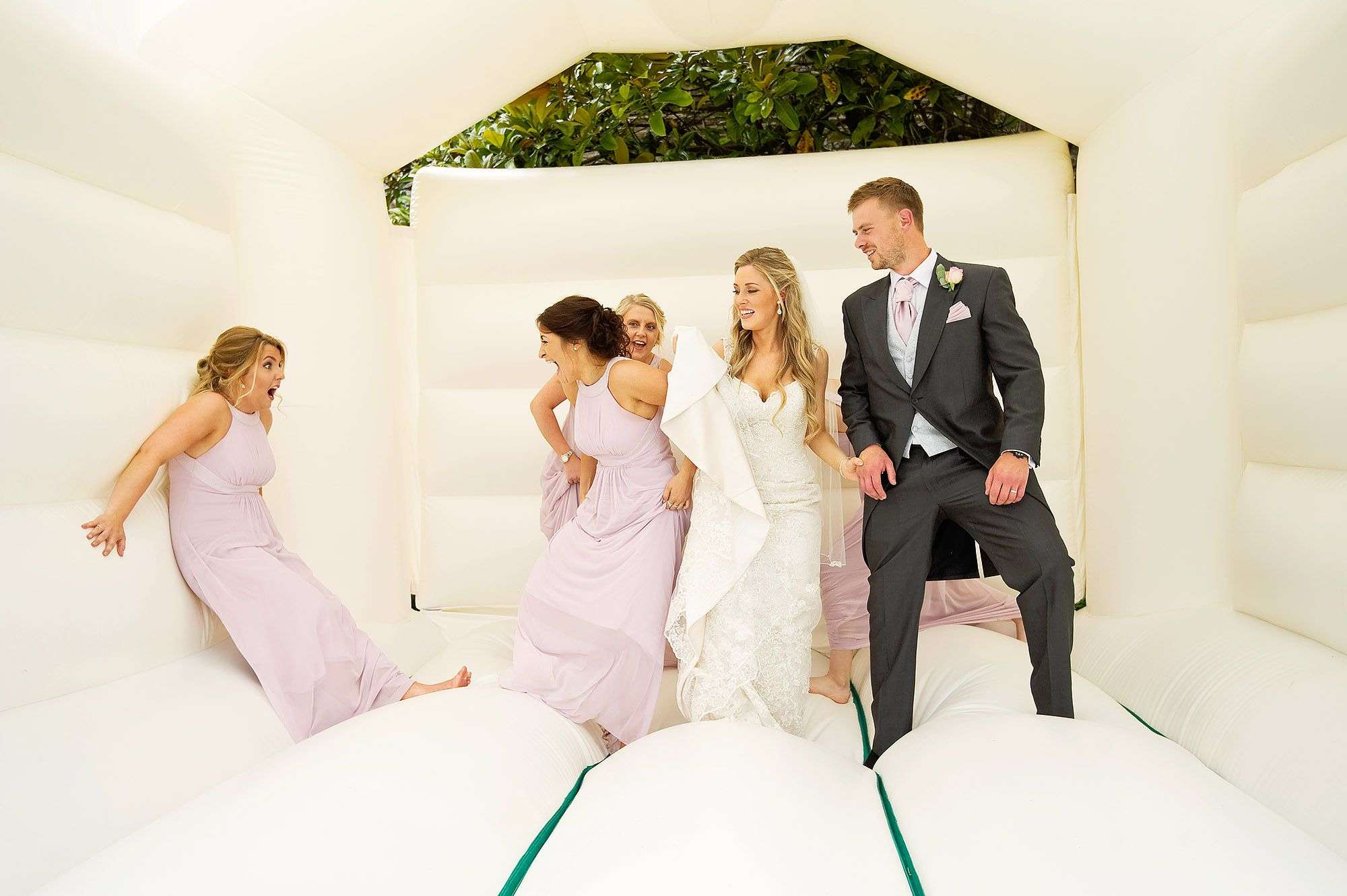 Bridesmaids and bride and groom on bouncy castle at Langdon Court in devon