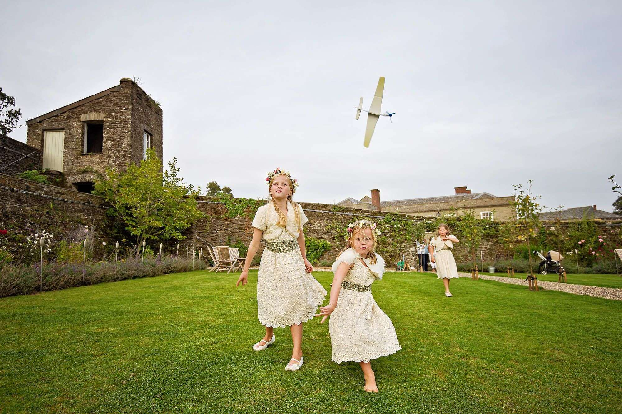Cheeky flowergirls at Shilstone House throwing model planes