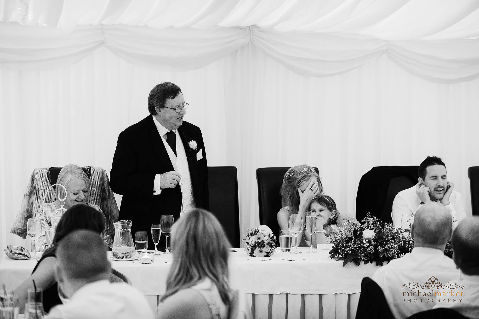 Funny Father of the bride speech by Devon wedding photographers as groom and bride show they are embarrassed