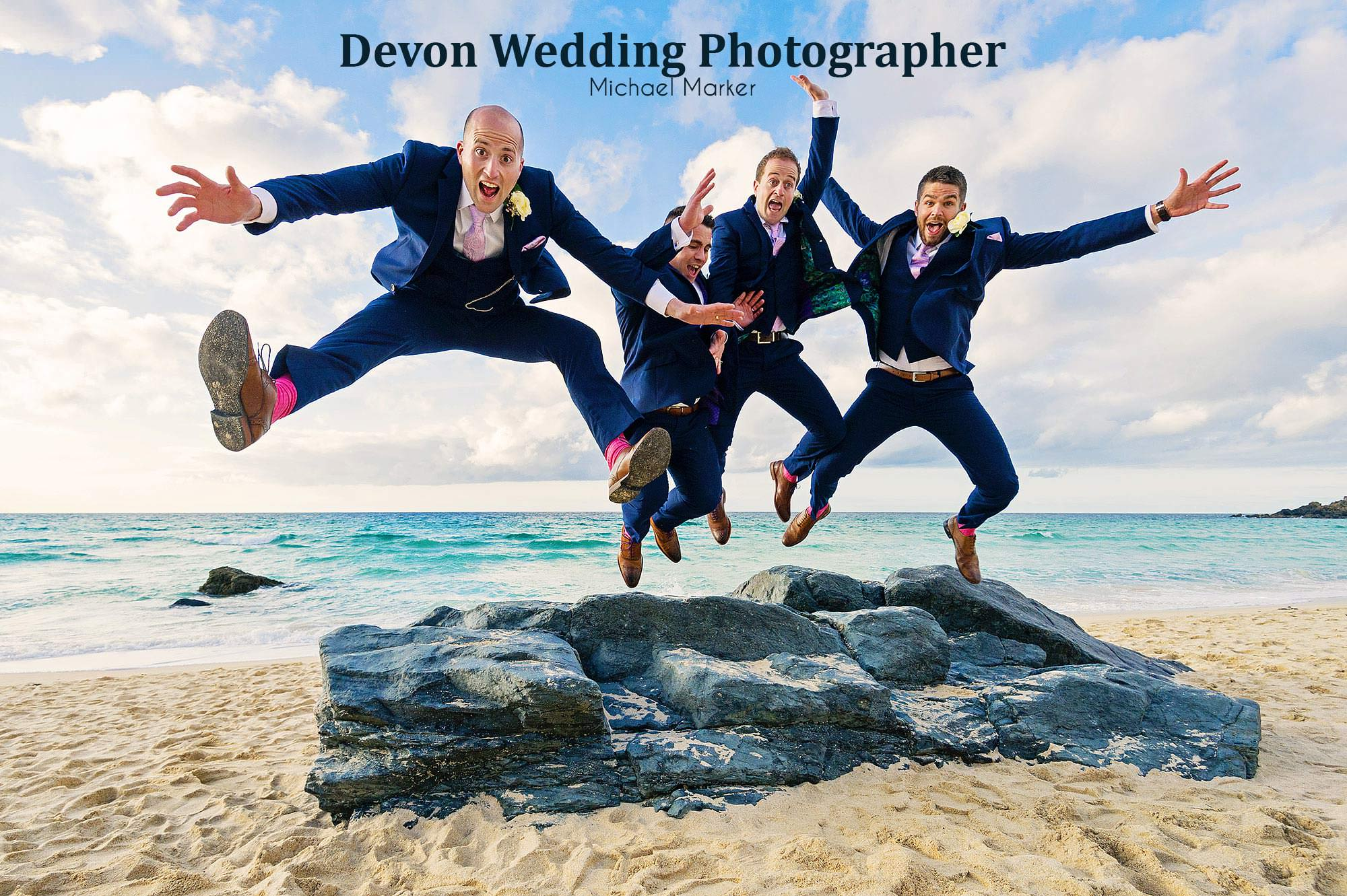 Groom and groomsmen jumping of rocks at porthmeor beach on the weddign day
