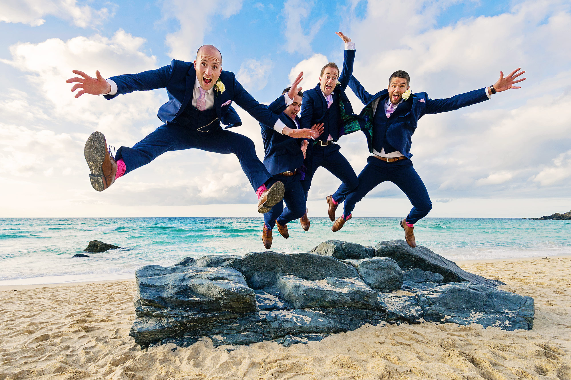 Groom and three groomsmen jumping for joy off rocks on Porthmeor Beach in St Ives Cornwall.