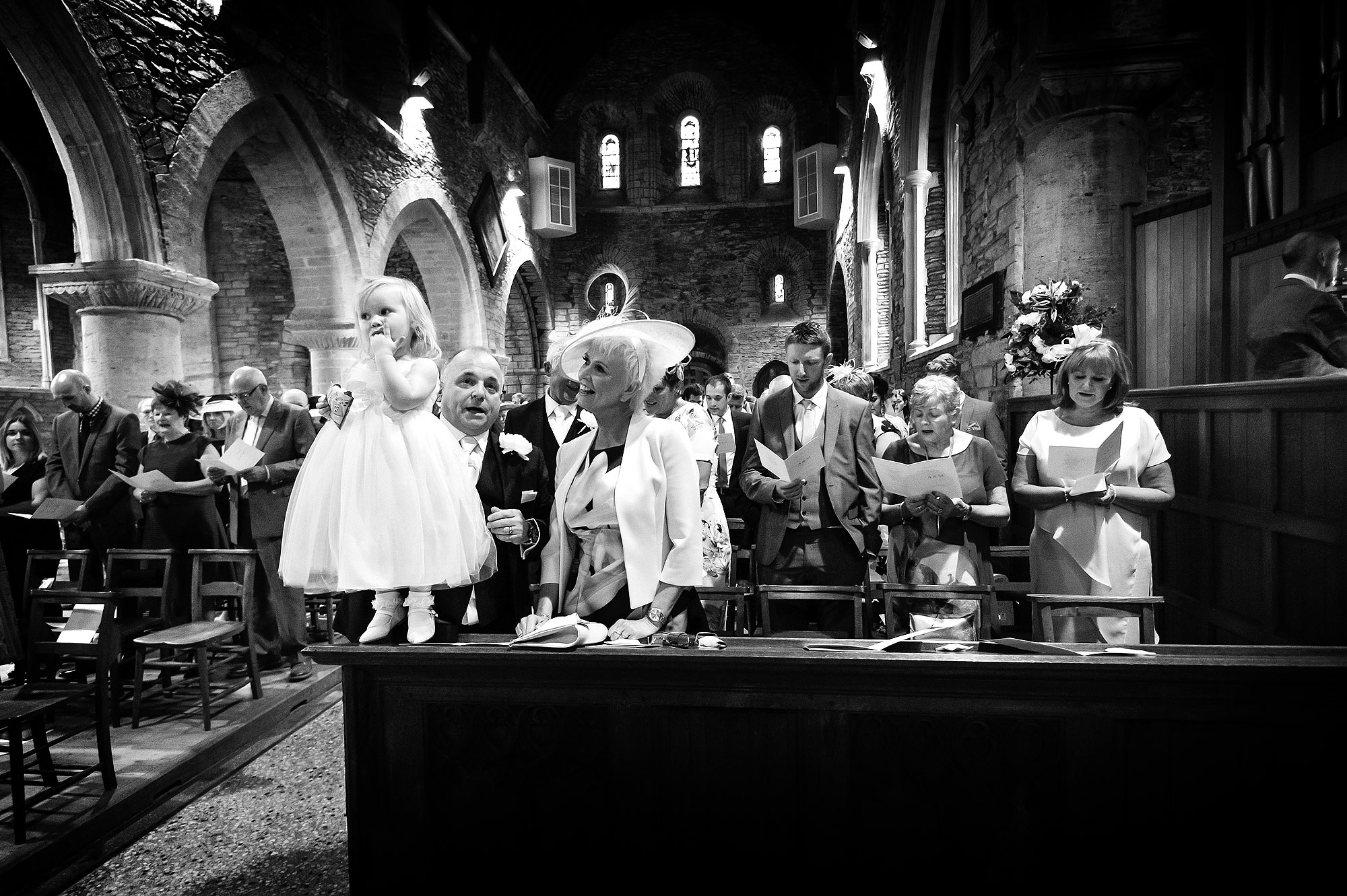 Flowergirl eating sweets during wedding ceremony at St Germans curch in Cornwall