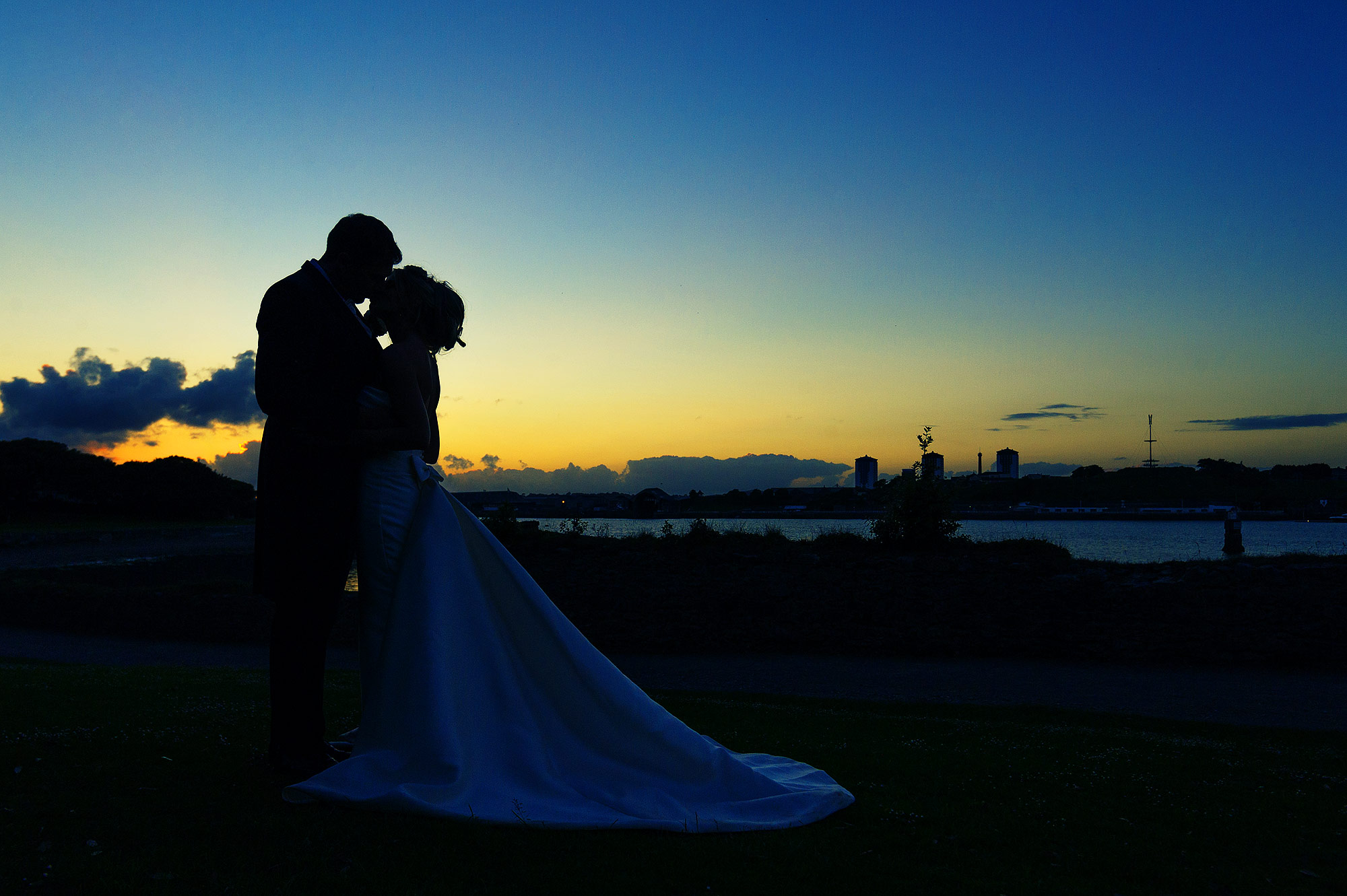 Bride and groom kiss on banks of the riverTamar in Cornwall for their wedding at Mount Edgcumbe Orangery.