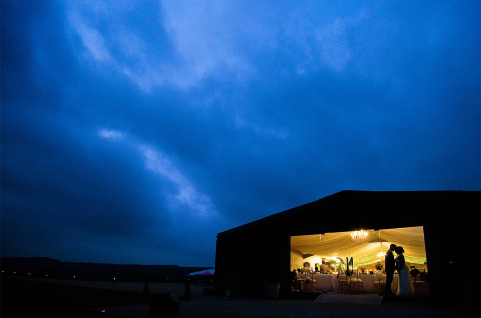 Bride and groom silhouetted in window of Axnoller Farm wedding reception barn at dusk