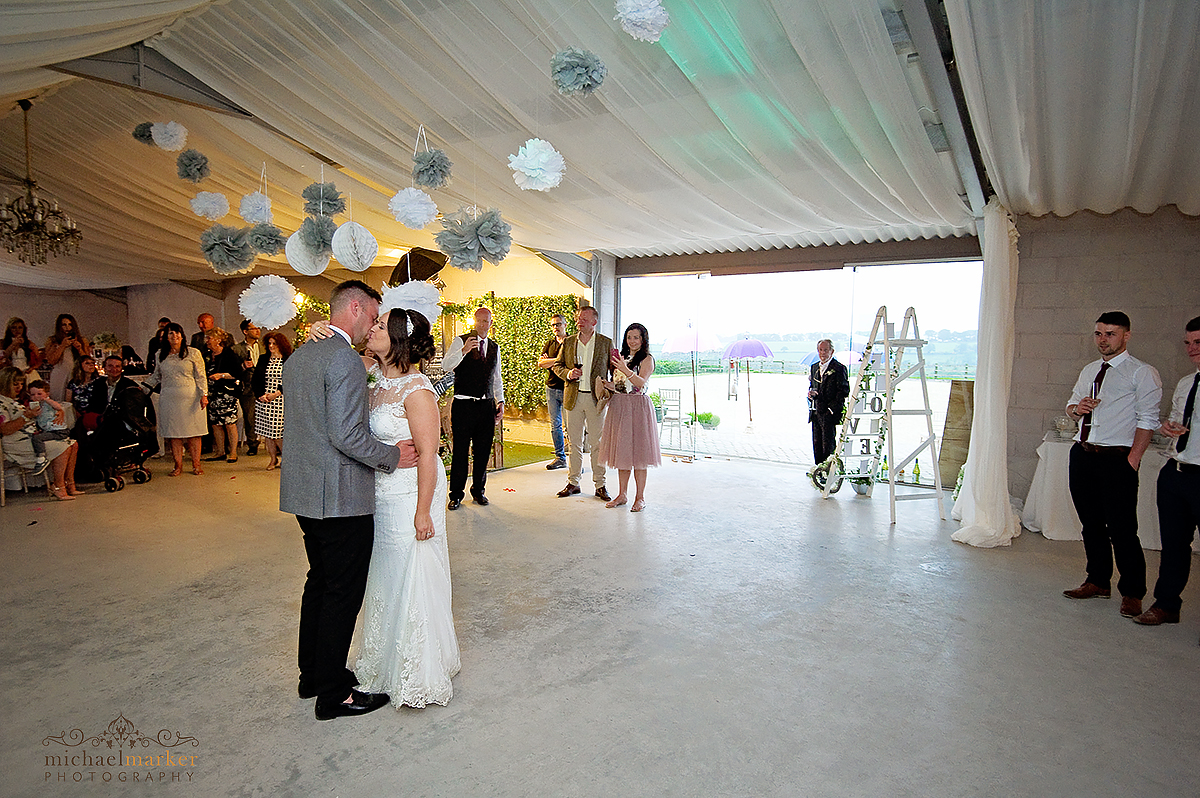Bride and groom kiss during their first dance at Axnoller farm