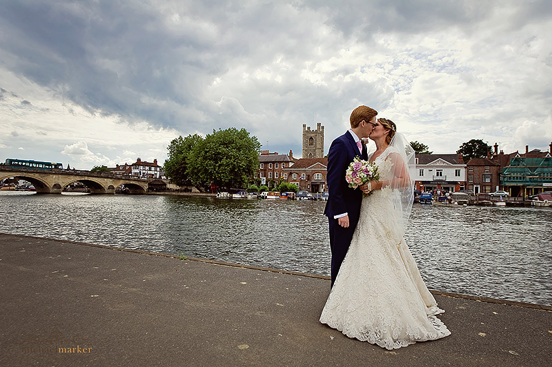 Bride and groom kiss by the River at Henley-on-Thames