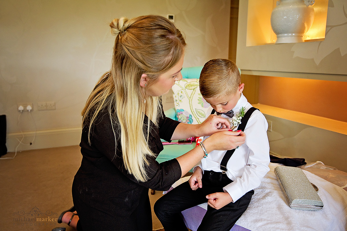 Helping page boy with his floral button hole at Axnoller Farm wedding in Dorset
