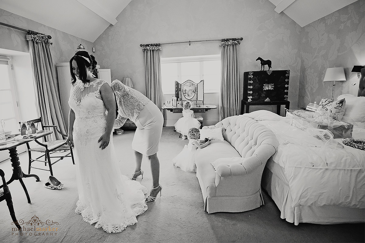 Mother of bride adjusting Bride's wedding dress in honeymoon suite at Axnoller Farm in black and white