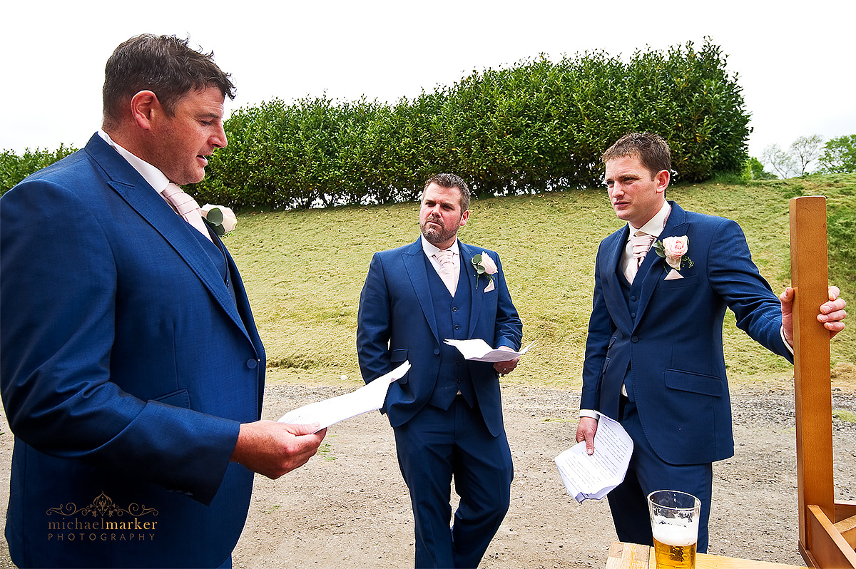 Documentary photo of bestmen preparing their wedding speeches outside before the wedding reception