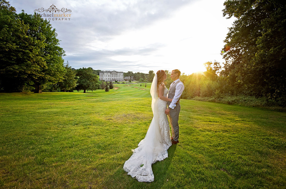 Bride and groom at sunset looking towards Moor Park