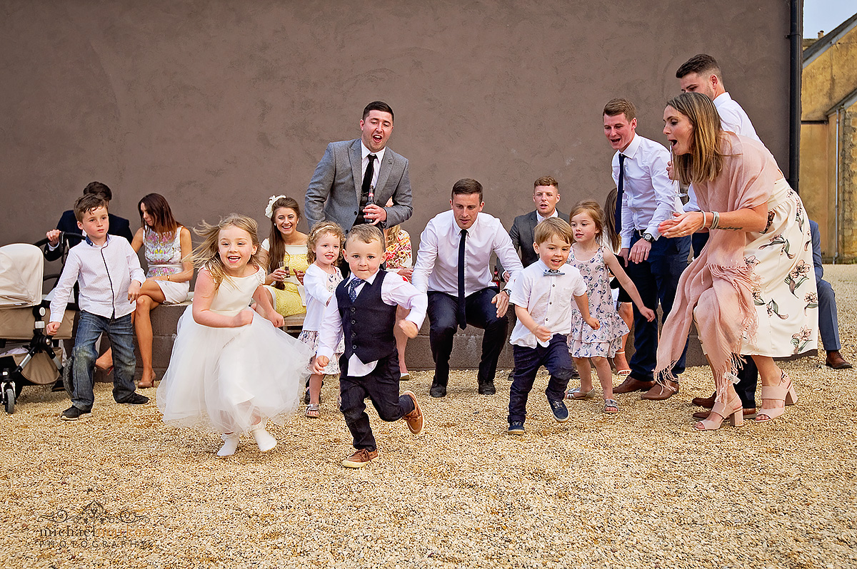 Children runnign a race at Axnoller farm wedding as parents cheer and watch
