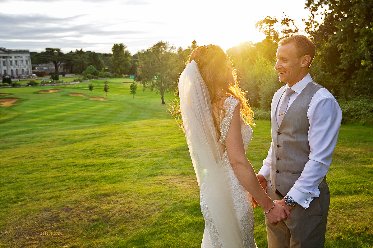 Bride and groom looking at each other at sunset with Moor Park in the background