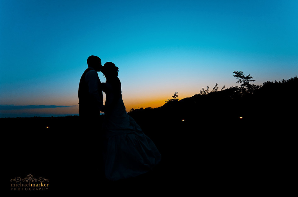 Sunset silhouette of bride and groom kissing