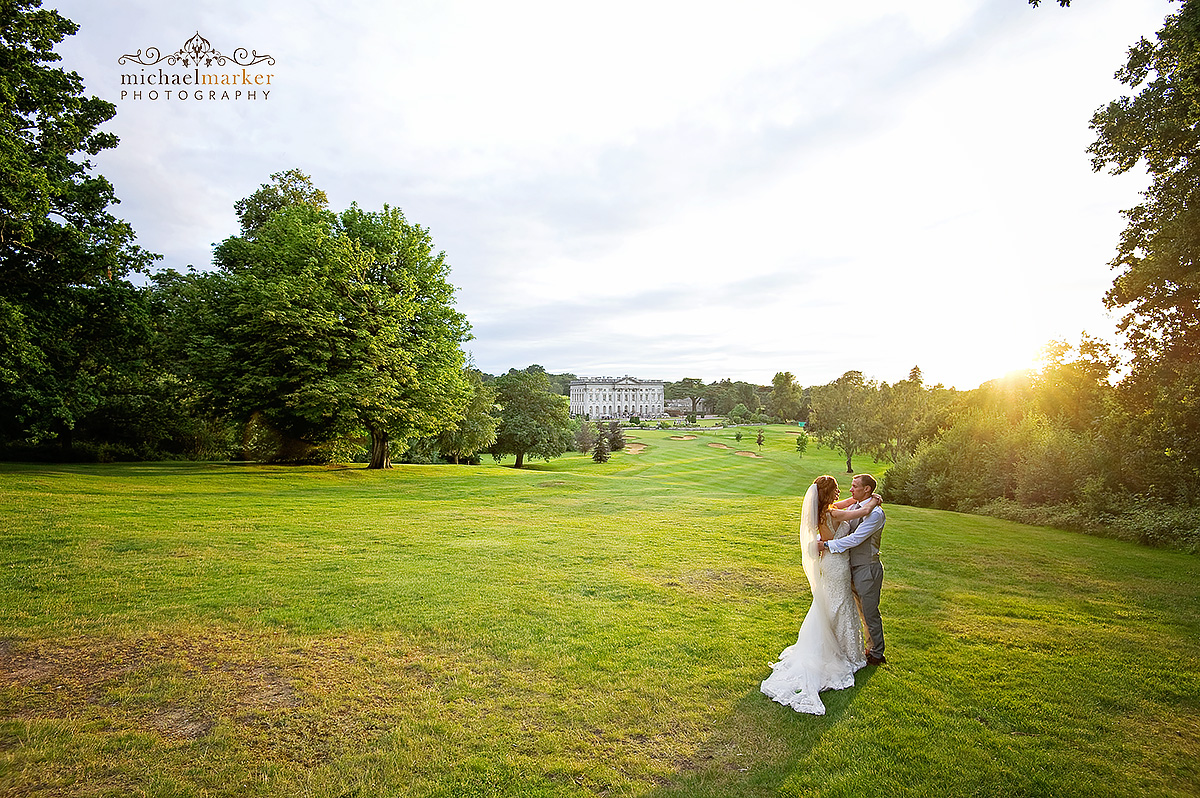 Bride and groom embrace as they look towards Moor Park House near London as the sunsets behind.
