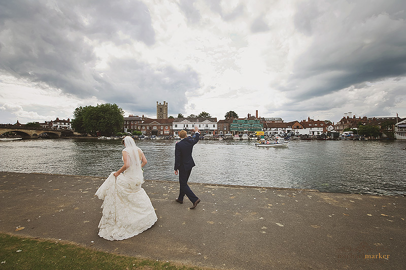 Bride and groom wave to paeer bys on the river at Henley-on-Thames wedding