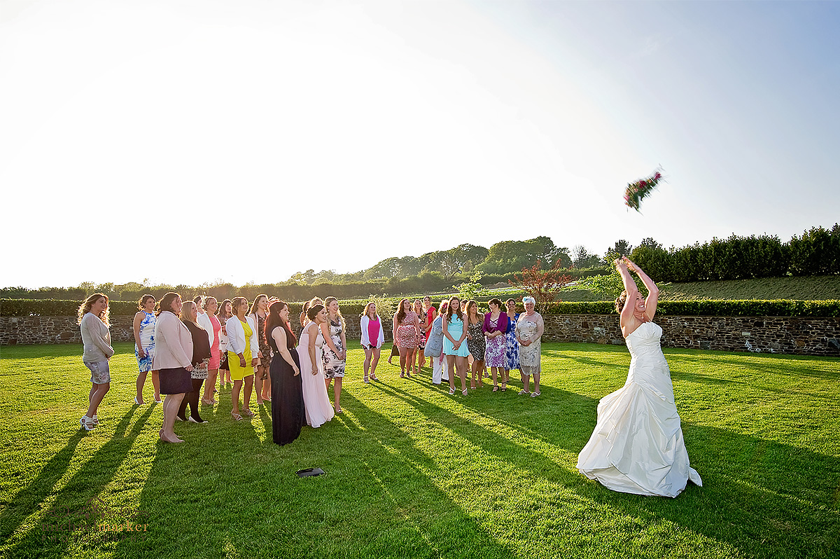 Bride throwing her wedding bouquet at Lifton farm shop